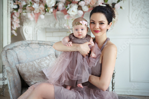 Fotografia  Happy smiling mother sitting with her little daughter in her arms in a chic interior