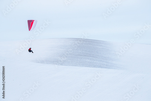 Male paraglider over snow covered hills of Palouse, USA