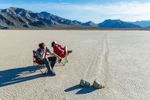 """Exciting Day At The Races"".  Two People Sit In Chairs Asleep While Watching The Very Slow Results Of Two Competing Boulders At The Racetrack In Death Valley National Park. The Area Gets Its Name From The Once Mysterious Tracks Which Are The Result Of Periodic Winter Storms Over Many Years That Brought Moisture To The Playa Followed By Cold Night Time Temperatures Which Then Formed Thin Sheets Of Ice And Then Are Pushed By High Winds, Nudging The Boulders A Little At A Time And Creating These Remarkable Tracks. Disclaimer: The Playa Is A Senstive Environment And The Site Of Theft And Vandalism. The Participants In This Photo Were Careful To Make Sure The Ground Was Dry And That The Chairs Left No Trace."