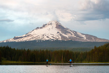 A Man And Woman Stand Up Paddleboard At Trillium Lake, A Popular Recreation Lake Near The Base Of Mount Hood, Oregon.