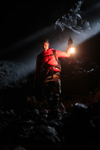 A Man Holding A Propane Lantern Descends Into The Cheese Cave, A 2,000 Foot Lava Tube That Was First Discovered In 1894 And Later Used For Cheese Storage By The Guler Cheese Company Near Trout Lake, Washington. We Lucked Out When We Visited The Cave On A Winter Day When The Sun Was At Just The Right Angle To Send A Shaft Of Light Straight Into The Opening Of The Cave Creating A Rare And Beautiful Moment.