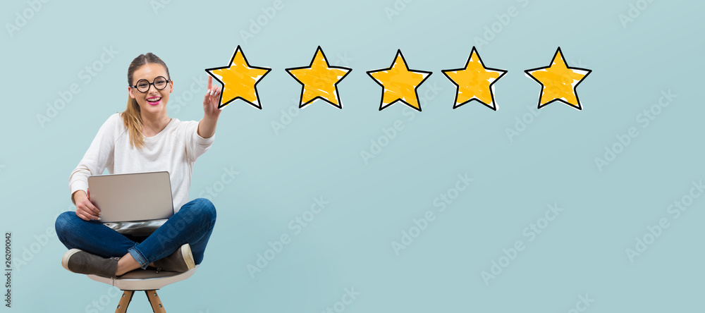 Fototapeta Five star rating with young woman using her laptop
