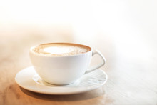 White Cappuccino Cup With With Latte Art Heart On Light Brown Wood Background Lit By Bright Morning Sunlight With White Copy Space