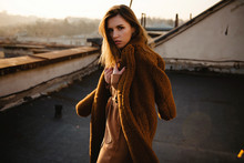 Fashion Shot Of Attractive Young Brunette Woman In Stylish Coat On The Rooftop With Beautiful City View On Sunset