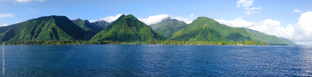 Fototapeta DRONE Flying over the deep blue sea and towards the towering mountains of Tahiti