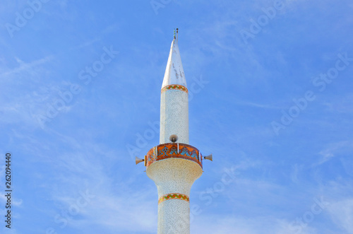 Fotografia  Amazing close up view of the white minaret tower taken from below against the blue sky
