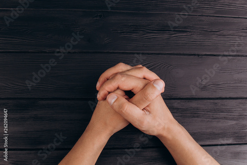 Fotografie, Obraz  interlocked fingers, white male hands interlocked on black rustic wood table close up
