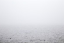 Misty Morning Over The Lake. Gray Thick Fog Over The Water Surface Closes The Horizon. Dull Day.