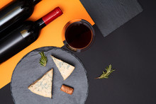 Composition Of Blue Cheese With Prosciutto Slices On Black Slate Board With Bottle Of Wine On Colorful Background