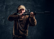 canvas print picture - Male hunter in cap and headphones holding a rifle and aiming at his target or prey. Studio photo against a dark wall background
