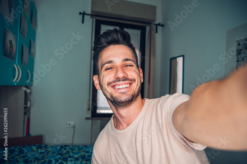Fotografie, Obraz  Handsome caucasian man taking a self portrait indoor at home