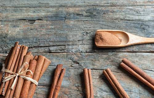 Fotografie, Obraz  Close up cinnamon sticks and cinnamon powder in wooden spoon on wooden table bac