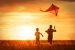 canvas print picture - Children with a kite at sunset