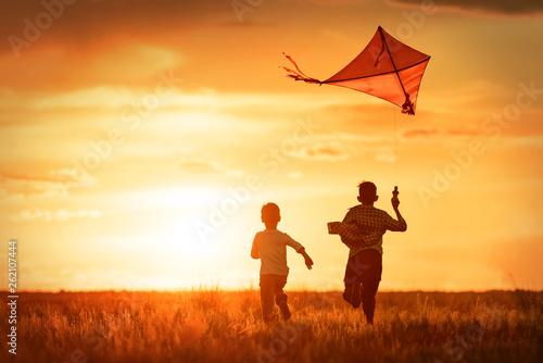 Obraz na plátně Children with a kite at sunset