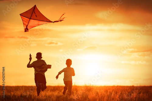 obraz PCV Children with a kite at sunset