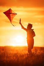 Boy With A Kite At Sunset