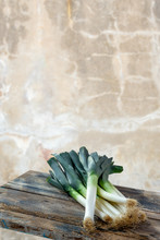 Fresh Organic Leeks Tied On An Old Wooden Board, Against Old White Wall