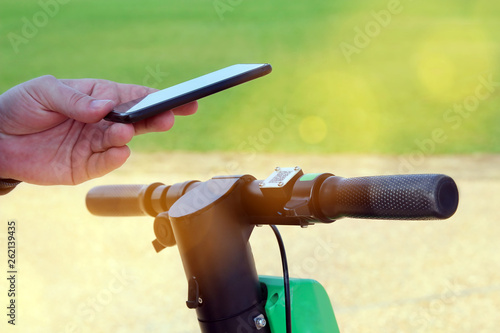 Fotografia, Obraz  Close up image of a man on an electric scooter paying online