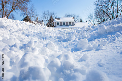 Snow drifts and chunks of snow piling up in winter with a house in the backgroun Tapéta, Fotótapéta