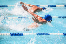 Men Swimming Butterfly Stroke In A Race, Focus On Water Droplets,  Swimmer Is Out Of Focus