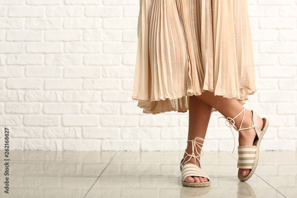 Fototapety, obrazy: Stylish young woman in shoes near white brick wall