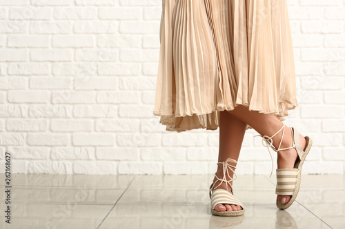 Fotografia  Stylish young woman in shoes near white brick wall