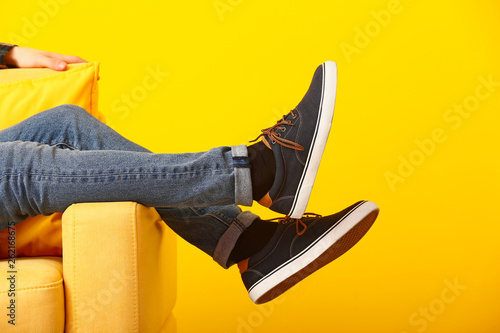 Stylish man in shoes sitting in armchair on color background Canvas Print
