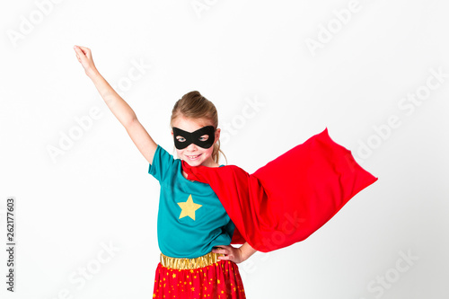 blond supergirl with black mask and red cape posing in front of white background Wallpaper Mural