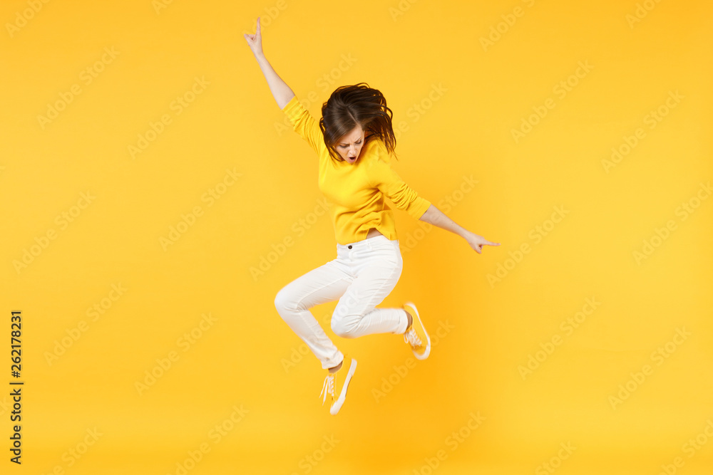 Fototapety, obrazy: Cheerful funny young woman in summer casual clothes jumping and spreading hands isolated on yellow orange wall background in studio. People sincere emotions, lifestyle concept. Mock up copy space.