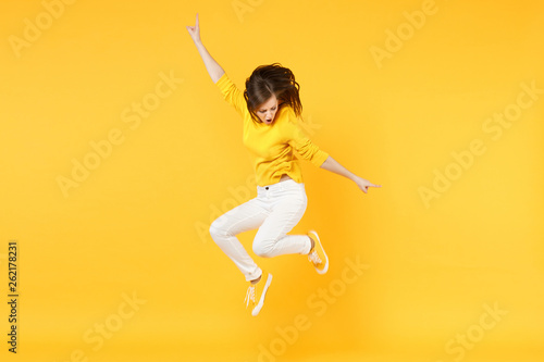 Fotografie, Obraz  Cheerful funny young woman in summer casual clothes jumping and spreading hands isolated on yellow orange wall background in studio