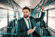 Smiling Caucasian businessman in suit driving in public bus and using smart phone. Someday it will make sense.