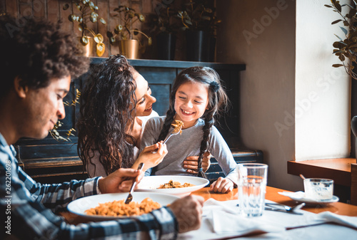 Fotografía  Happy african american family eating lunch together at restaurant and having fun