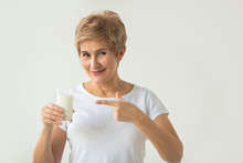 Beautiful Elderly Woman In A White T-shirt With A Glass Of Milk On A White Background With A Gesture Of Hand