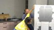 Young couple unpacking new fridge from box at new home