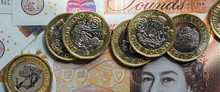 British Economy And Currency Exchange Concept With Macro Close Up On One Pound Coins Over A 10 GBP Bank Note In A Web Banner Format.