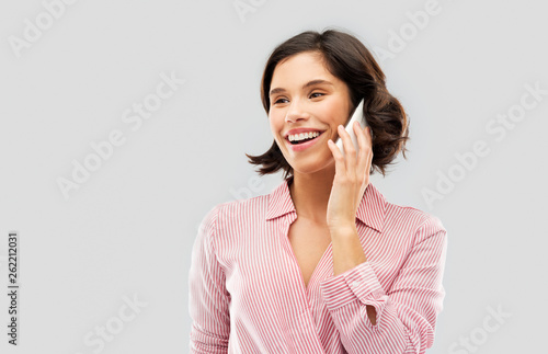 fashion, style and people concept - happy smiling young woman in striped shirt calling on smartphone over grey background