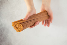 Top View Of Woman Hand Holding Italian Uncooked Spaghetti Whole Grain Pasta. Italian Food, Selective Focus