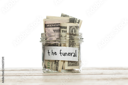 Saving jar with money for the funeral on white wooden table isolated Canvas Print