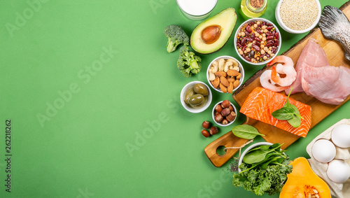 Fotografia  Mediterranean diet concept - meat, fish, fruits and vegetables on bright green b
