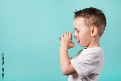 Foto child drinks water on a turquoise background