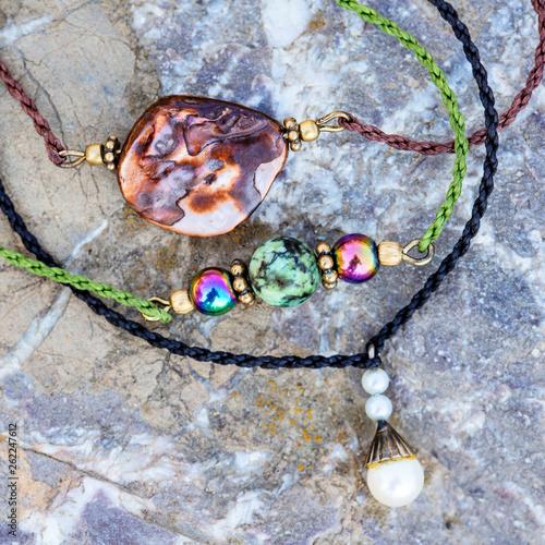 Fotografía  Natural stone bead tiny three bracelets on rocky background