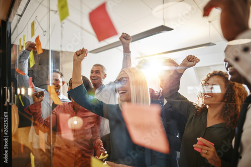 Cheering businesspeople brainstorming with sticky notes in an of