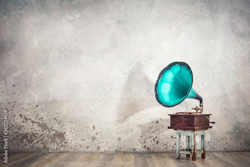 Fotobehang Muziekwinkel Vintage antique aged aquamarine gramophone phonograph turntable on aged wooden stool front concrete wall background with its shadow. Retro old style filtered photo