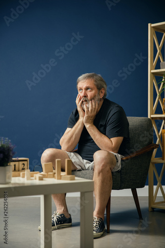Terrified and afraid of his self. Old bearded man with alzheimer desease has problems with his hands motor skills. Concept of illness, memory loss due to dementia, healthcare, neurological disorder. Wall mural