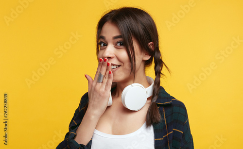 Fotografia  Surprised female teenager expresses great confusion, keeps hand on mouth, stares at camera, isolated over pink background