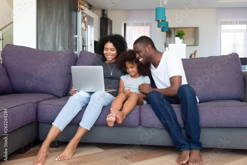 Happy African American family with daughter using laptop at home Tablou Canvas