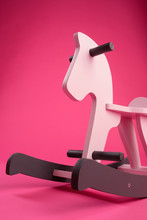 Wooden Children's Rocking Horse On A Colored Background