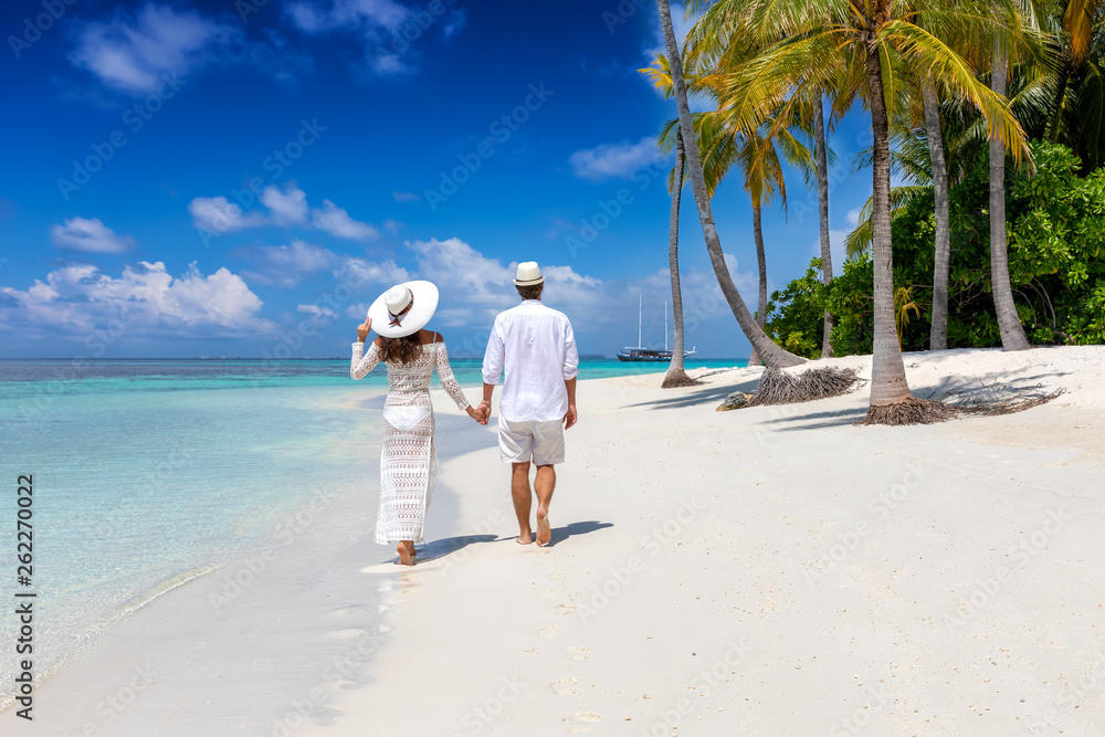 Fototapeta Elegant traveler couple walks down a tropical beach with coconut palm trees and turquoise waters in the Maldives islands