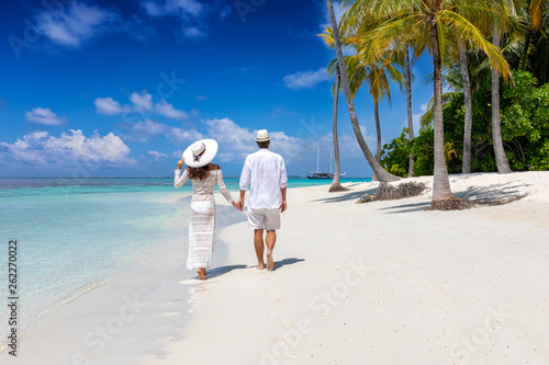 Elegant traveler couple walks down a tropical beach with coconut palm trees and Fototapeta