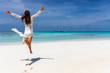 Happy traveler girl in white summer dress enjoys the tropical paradise beach with turquoise sea in the Maldives